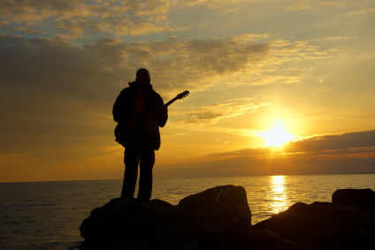 lonely guitarist on the evening beach and sundown